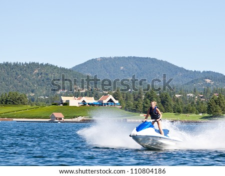 Beautiful woman out on the lake riding a wave runner on bright sunny day