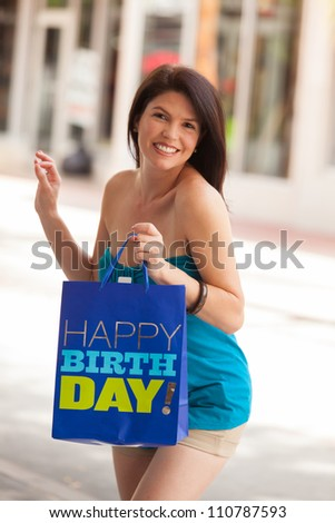 Beautiful woman outdoors in a shopping mall holding a happy birthday bag.
