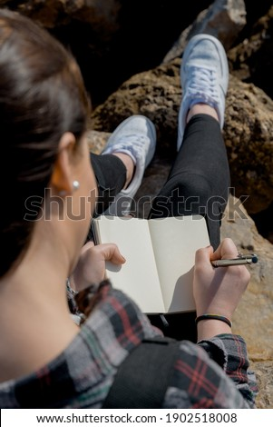 beautiful woman outdoors, writes in her notebook, stories and thoughts for her book to be published. lifestyle concept Photo stock ©
