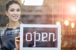 Beautiful woman owner stands and opens a wide sign through the shop window and smile. Small business, grocery store, prevent, minimise, reuse and recycle waste concept.