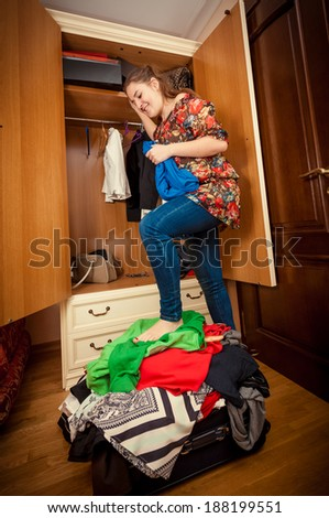 Beautiful woman packing suitcase on holiday at wardrobe