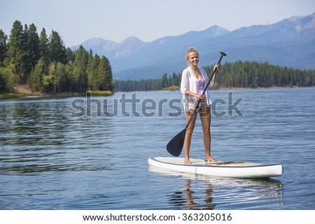 Beautiful woman paddle boarding on scenic mountain lake