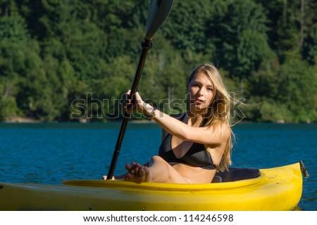 Beautiful Woman Paddling Yellow Canoe #114246598