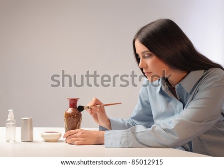 Beautiful woman painting a ceramic vase