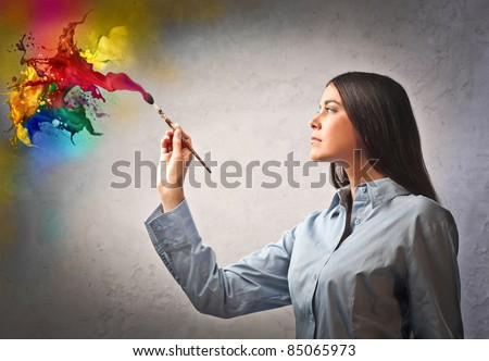 Beautiful woman painting with a paintbrush