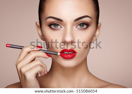 Beautiful woman paints lips with lipstick. Beautiful woman face. Makeup detail. Beauty girl with perfect skin. Red lips and nails manicure