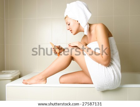 beautiful woman pampering herself in the bathroom after the shower and applying body lotion