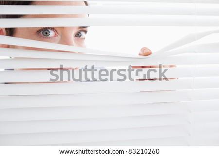 Beautiful Woman peeking out of a window in an office