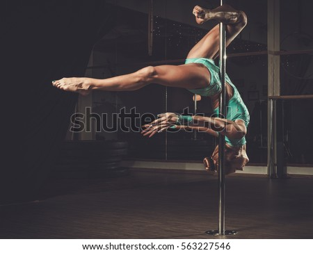 Beautiful woman performing pole dance on pole #563227546