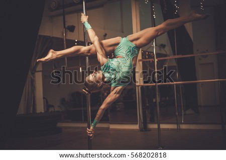 Beautiful woman performing pole dance on pole.