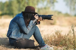 beautiful woman photographer with a camera taking photos