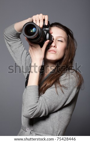 Beautiful woman photographer with camera at hands