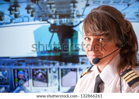 Beautiful woman pilot wearing uniform with epauletes, headset sitting inside airliner with visible cockpit during flight.