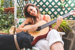 Beautiful Woman Playing Guitar Outdoors. Spanish Woman Playing Guitar with her Dog. Playing Spanish Guitar. Lifestyle Concept.