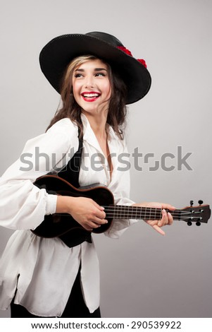 Shutterstock beautiful woman playing guitar with expression in zorro hat