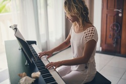 Beautiful woman playing piano inside of house with white curtains.
