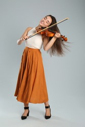 Beautiful woman playing violin on grey background