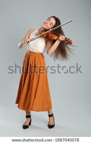 Beautiful woman playing violin on grey background Сток-фото ©