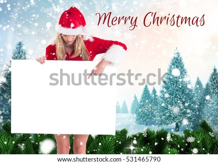 Beautiful woman pointing a blank placard against merry christmas wishes 3D #531465790