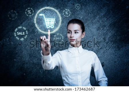 Beautiful Woman Pointing at Glowing Shopping Cart Icon. Perfect Online Shopping Business Concept