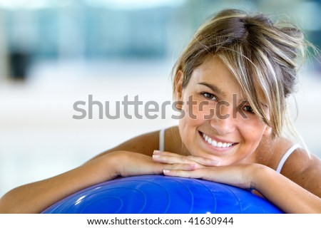 beautiful woman portrait at the gym smiling leaning on a pilates ball