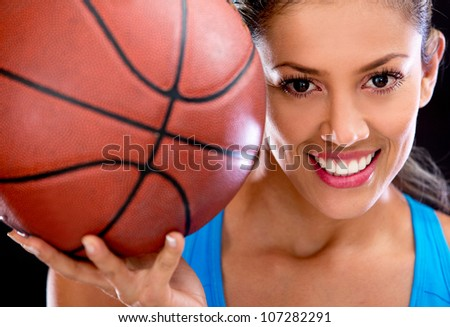 Beautiful woman portrait holding basketball and smiling