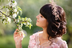 Beautiful woman portrait in airy pink dress sit on a branch of blooming apple tree. Pretty young caucasian girl plays with her dress. Girl dance in flowing dress. Romantic scene in spring garden
