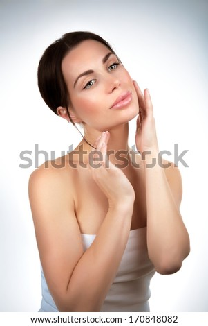 Beautiful woman portrait in the studio, touching face, using facial cream, natural cosmetics, perfect complexion, purity and beauty concept - stock photo