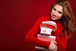Beautiful woman portrait on red background. Christmas lady with a gift.