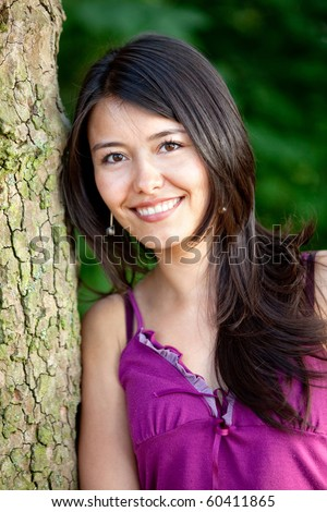 Beautiful woman portrait outdoors leaning on a tree and smiling