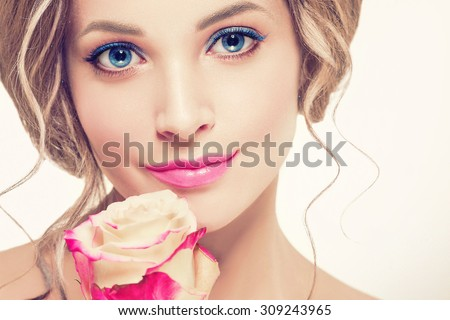 Beautiful woman portrait with perfect make up pink lips and nails blue eyes and rose flower