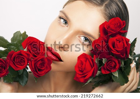 Stock Photo Beautiful woman portrait with red roses. Toned in warm colors, studio shot, horizontal