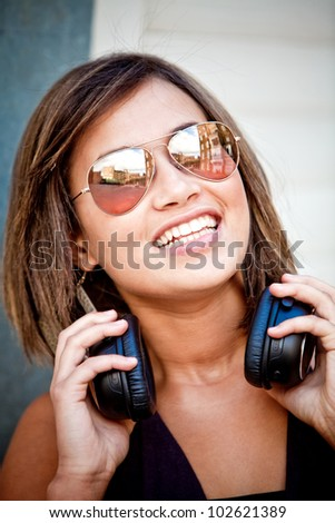 Beautiful woman portrait with sunglasses and headphones outdoors