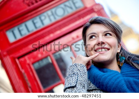beautiful woman posing calling hand gesture with a London phonebox behind her - stock photo