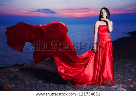 Beautiful woman posing in a luxurious red dress with a long train standing at the cliff against the sea.