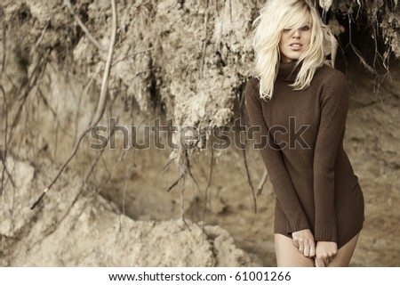 Beautiful woman posing in brown sweater against a cliff