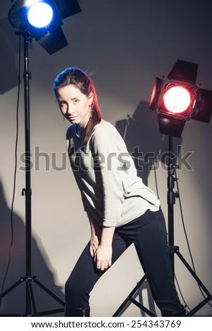 Beautiful woman posing in studio in light flashes