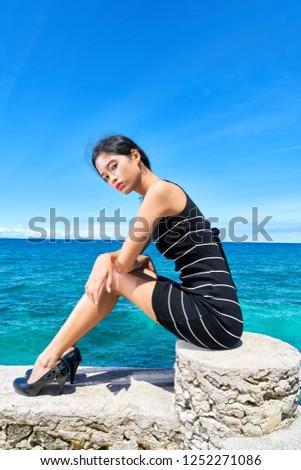 Beautiful woman posing - sitting on rock, introspection