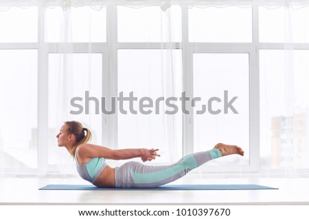 Beautiful woman practices yoga asana Salabhasana - locust pose at the yoga studio