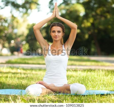 beautiful woman practices yoga in nature lotus pose