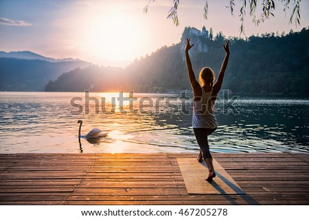 Beautiful woman practicing Yoga by the lake - Sun salutation series - Swan passing by - Toned image ストックフォト ©