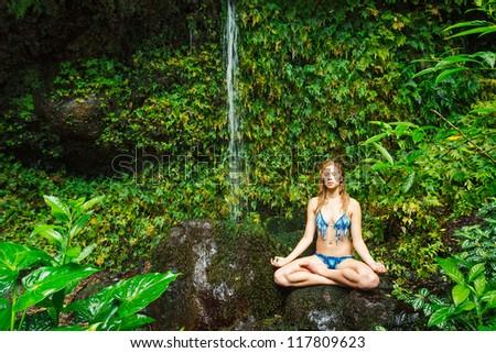 Beautiful Woman Practicing Yoga on Rock near Tropical Waterfall