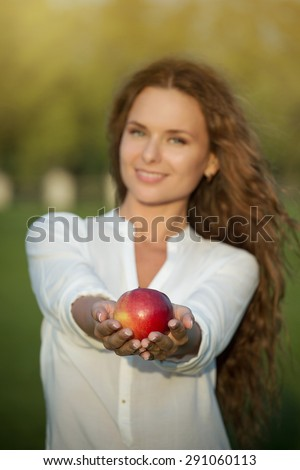 Beautiful woman presenting red apple. Lady with brown long hair smiling for camera.