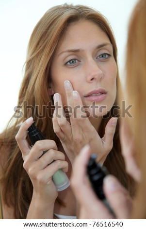 Beautiful woman putting foundation on her face