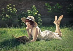 beautiful woman reading a book in the garden