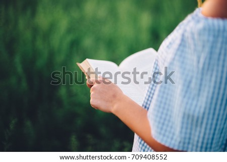 beautiful woman reading a book in the nature #709408552