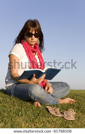 Beautiful woman reading a book on the park