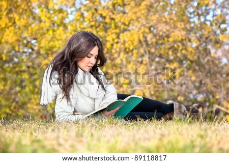 Beautiful woman reading the book on grass in autumn colored park