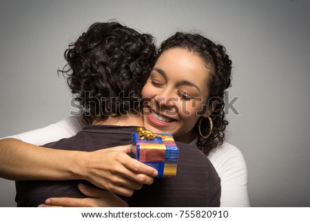 Beautiful woman receives Christmas gift. Happy girlfriend hugging her boyfriend affectionately. Close up.