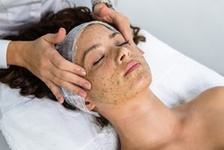 Beautiful woman receiving natural green peel facial mask with rejuvenating effects in spa beauty salon.
